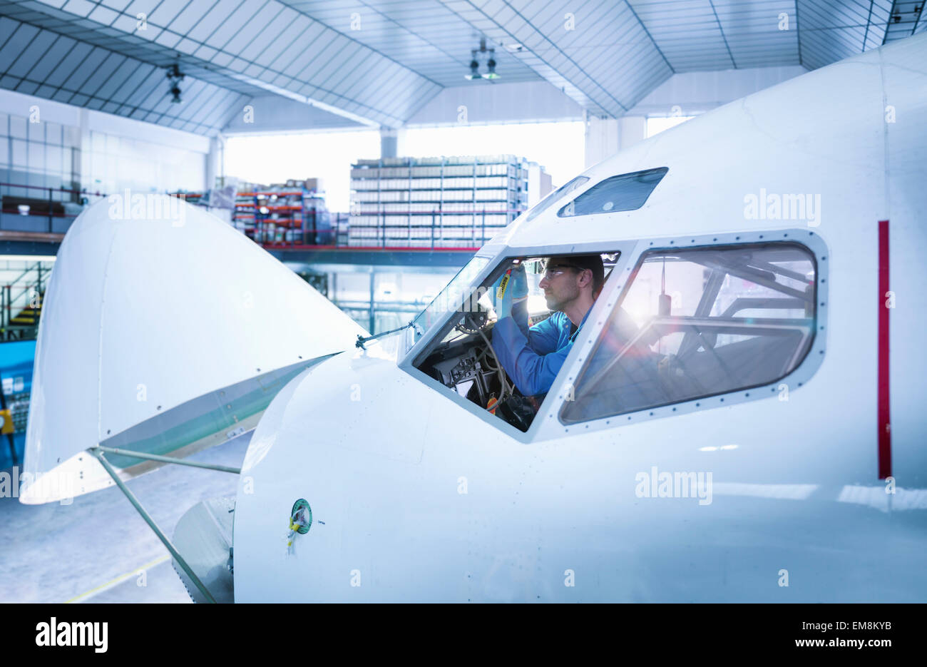 Engineer working in aircraft cockpit in aircraft maintenance factory - Stock Image