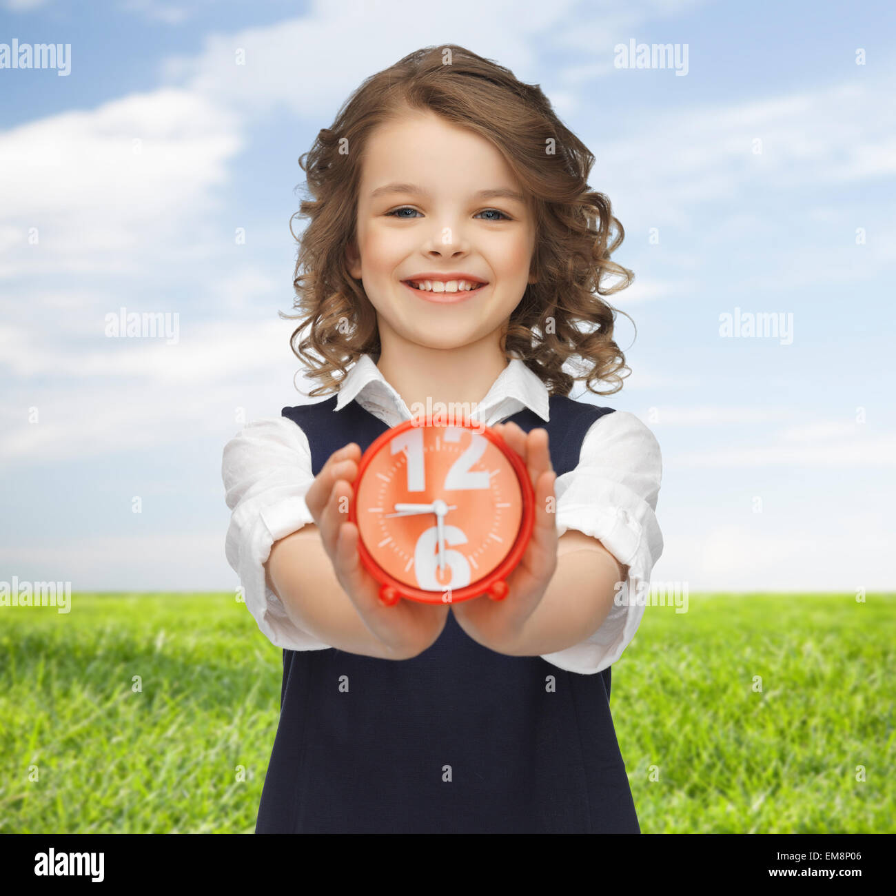 happy girl with alarm clock over summer background - Stock Image