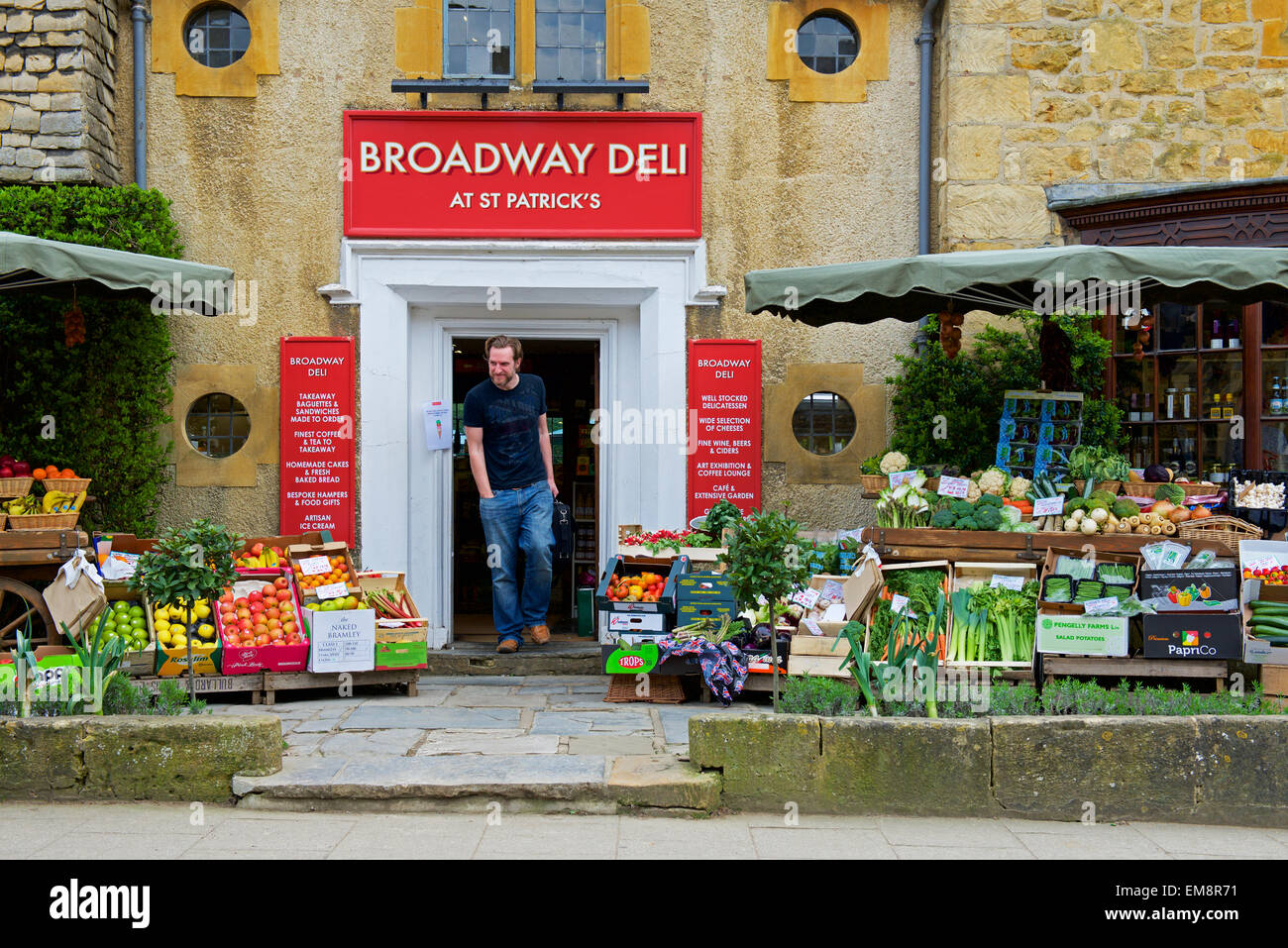 Man walking out of the Broadway Deli, in the Cotswolds village of Broadway, Worcestershire, England UK - Stock Image