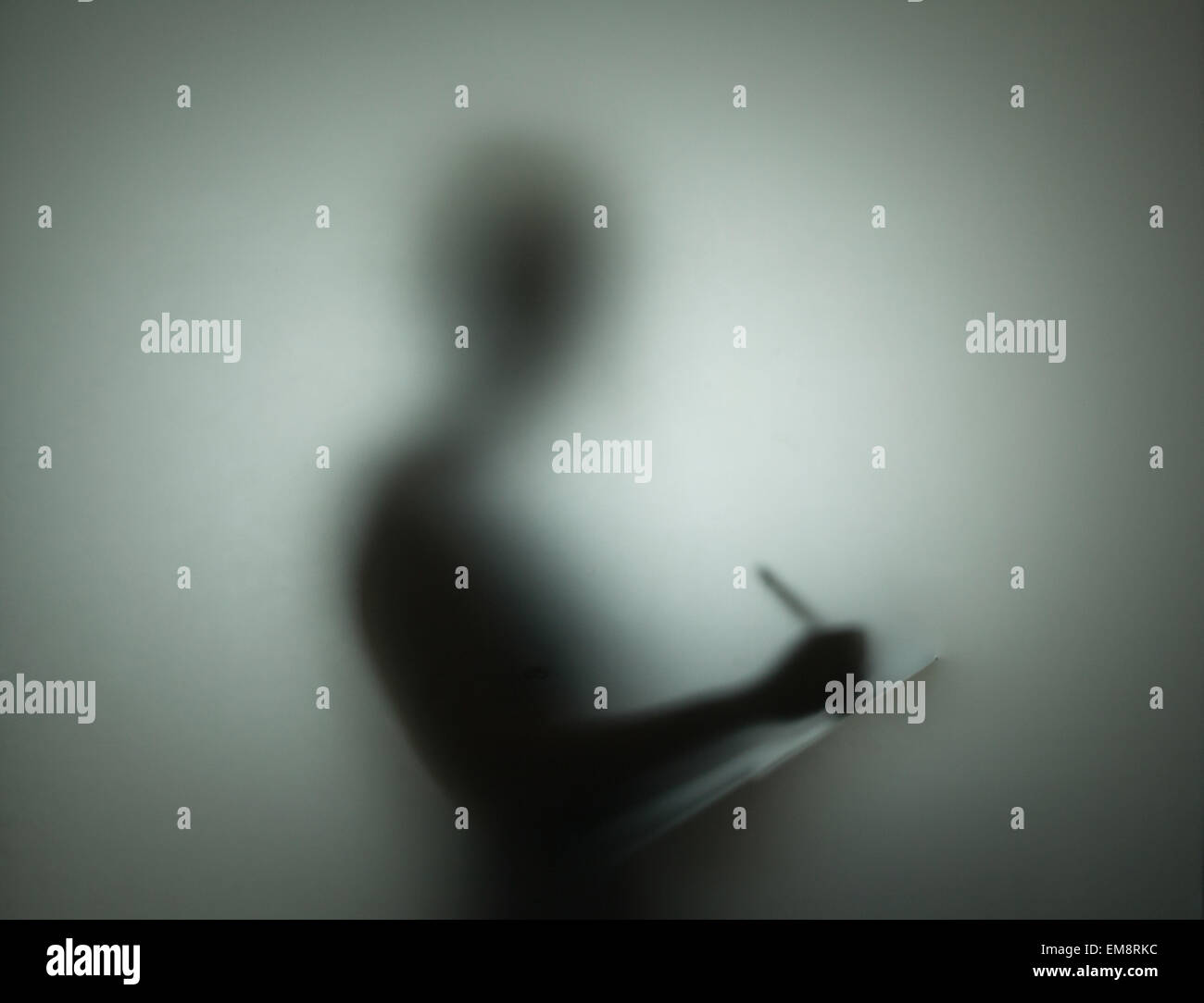 Silhouette of person using pen and clipboard, behind glass - Stock Image