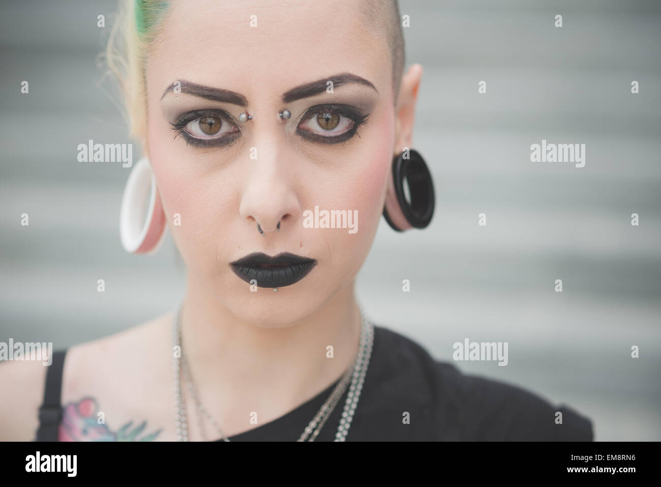 Portrait of young female punk with nose and earlobe piercings - Stock Image