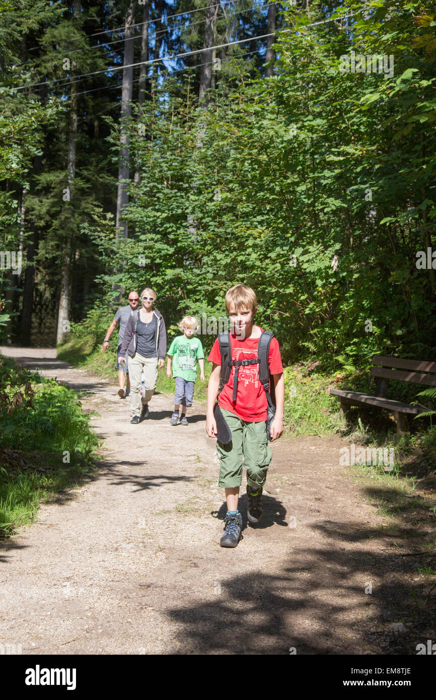 Parents and children hiking on forest path, Berchtesgaden, Obersalzberg, Bavaria, Germany - Stock Image
