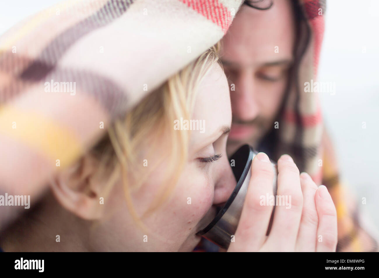 Couple outdoors, under blanket, drinking hot drink from drinks flask - Stock Image