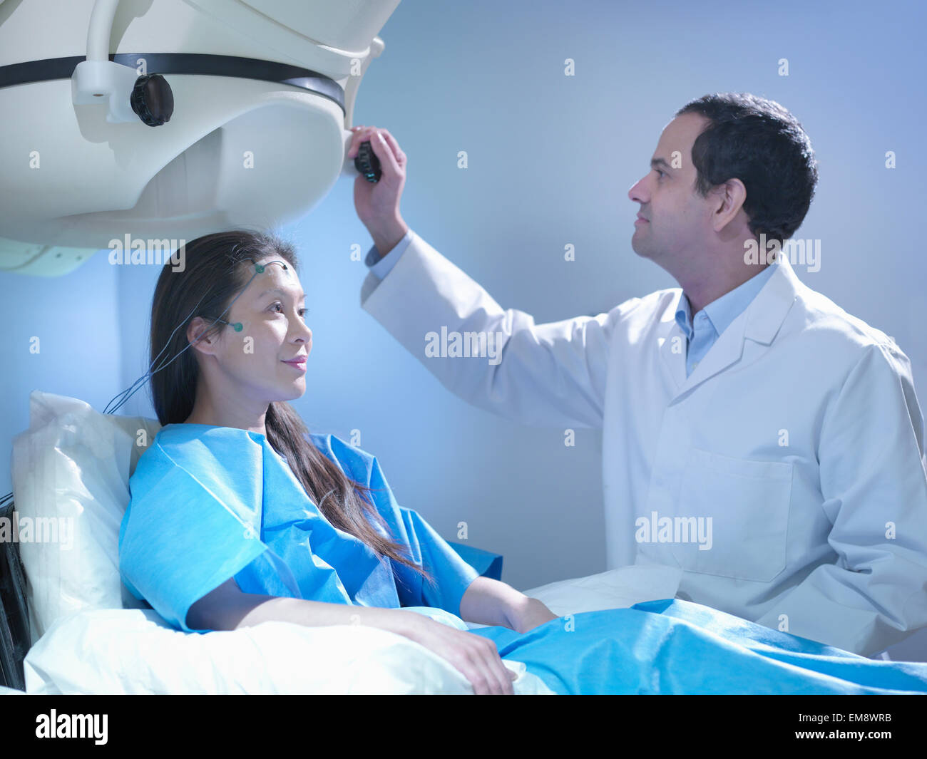 Doctor treating patient using magnetoencephalography (MEG) scanner - Stock Image
