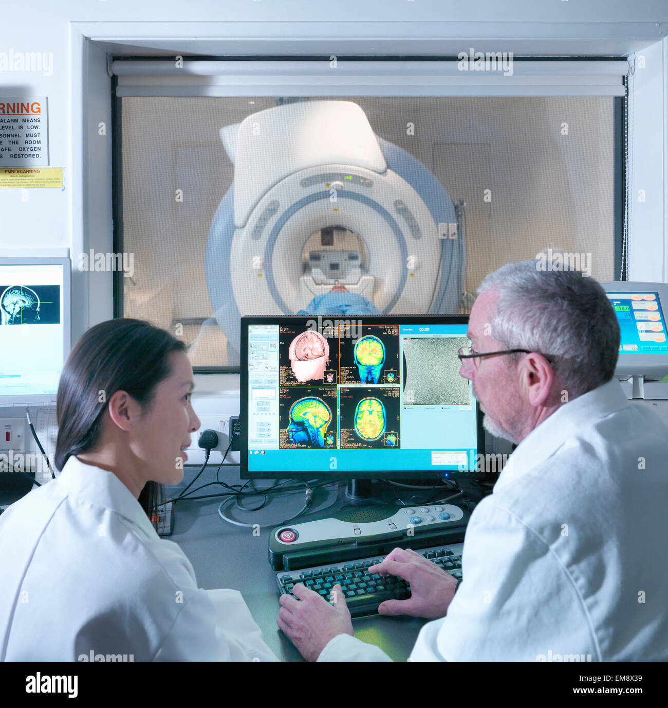Doctor and scientist with Magnetic Resonance Imaging (MRI) 3 Tesla twin speed scanner - Stock Image