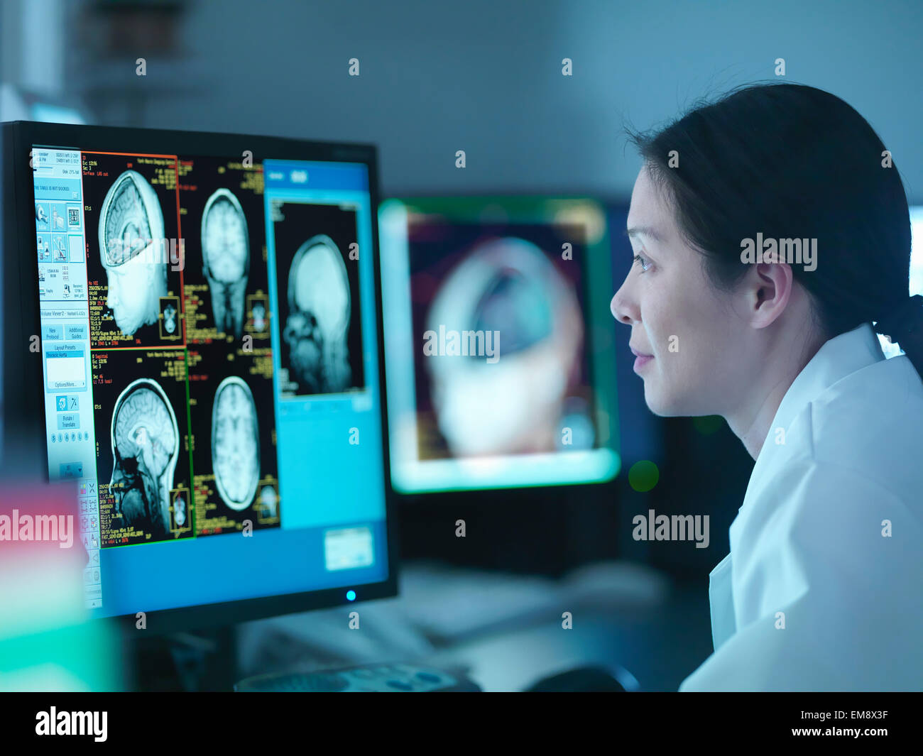 Scientist looking at 3D rendered graphic scans from Magnetic Resonance Imaging (MRI) scanner, close up - Stock Image