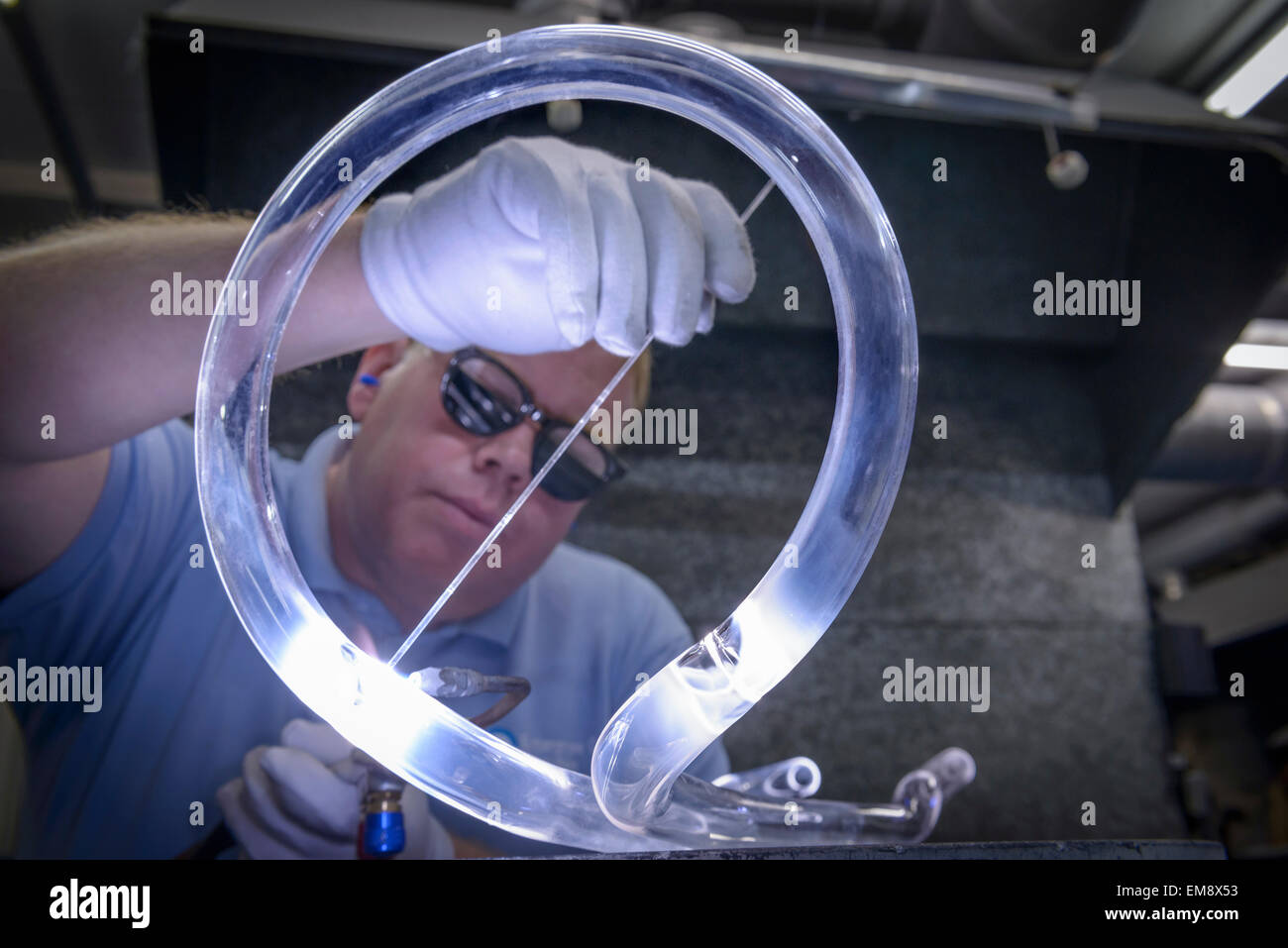 Industrial glass blower welding glass tubes - Stock Image