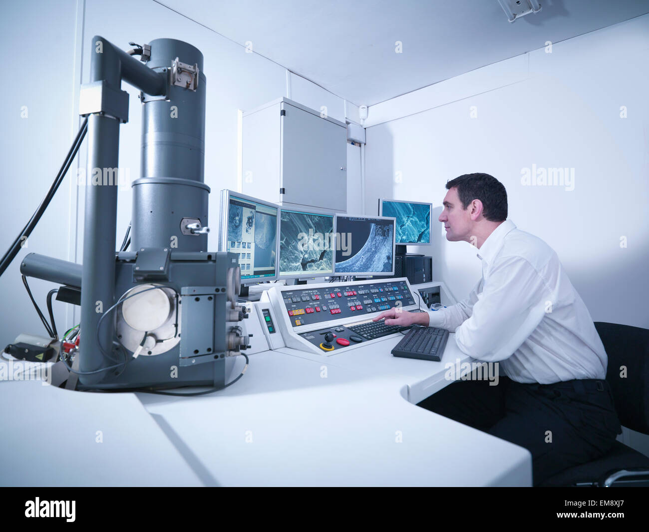 Metallurgist working with electron microscope in automotive test facility - Stock Image