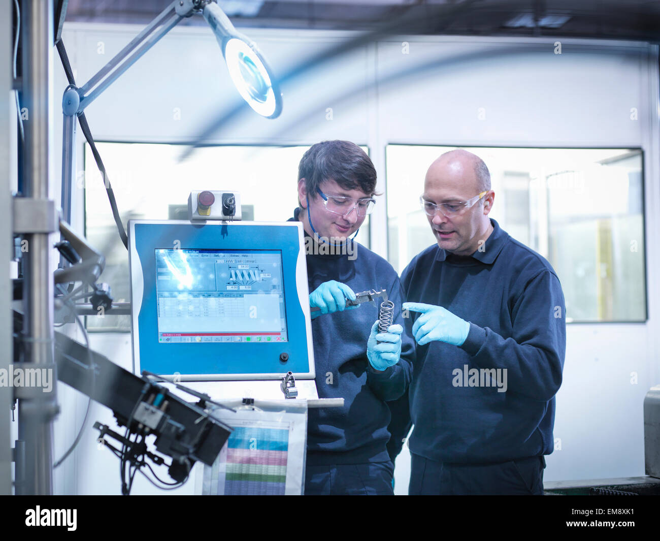 Apprentice with engineer in automotive parts factory - Stock Image