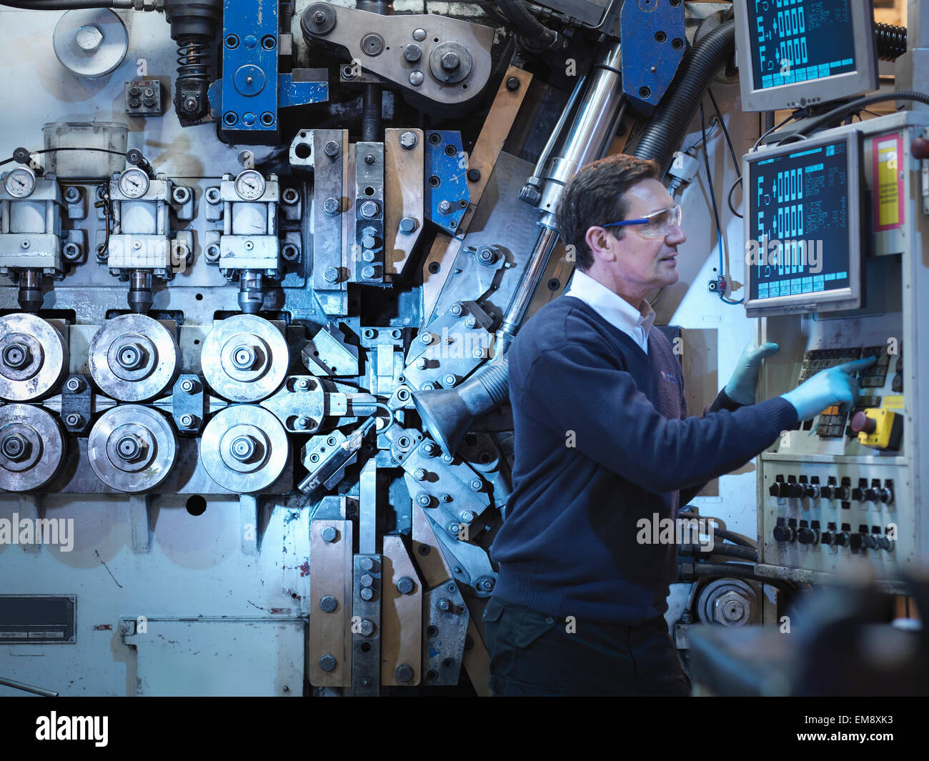 Engineer with machinery in automotive parts factory - Stock Image