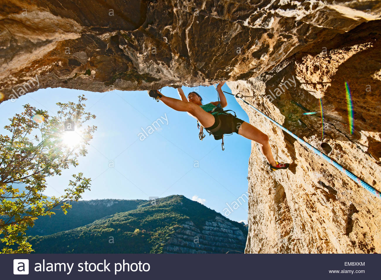 Female climber, climbing out of a cave with an old quarry in the background, Finale Ligure, Savona, Italy - Stock Image