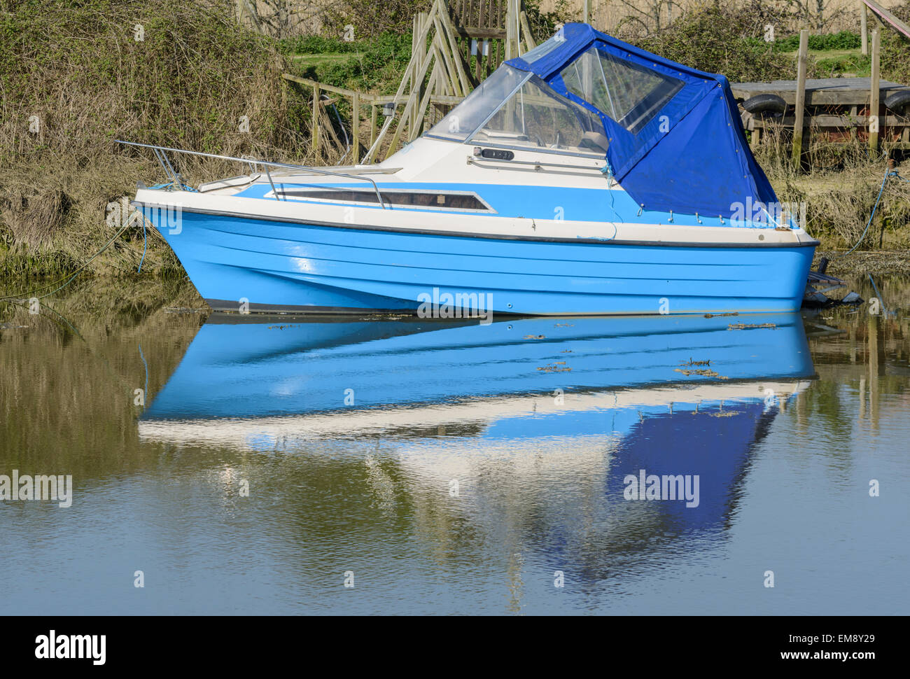 Small blue pleasure boat moored on a river with it's reflection in the water. - Stock Image