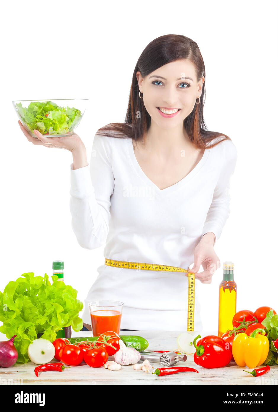Young happy woman with salad, measuring her waistline. Healthy food ans lifestyle concept. - Stock Image