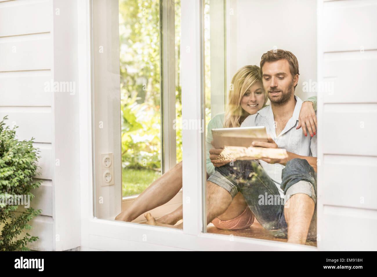 Mid adult couple sitting on floor using digital tablet at house window - Stock Image