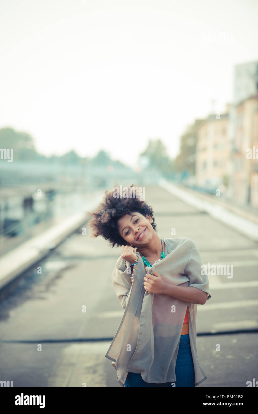 Portrait of young woman with head cocked in city industrial area - Stock Image