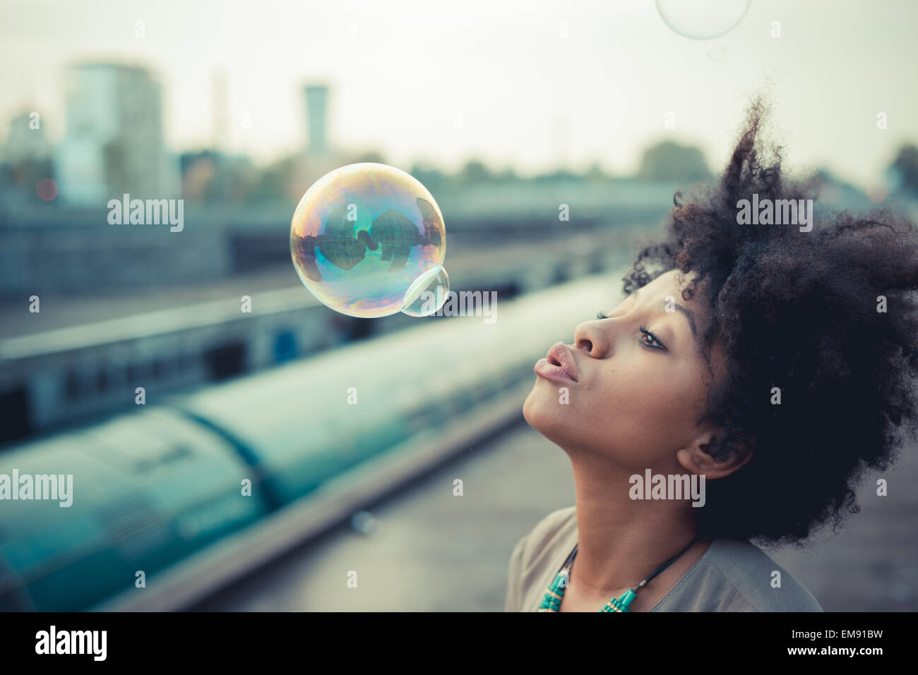 Young woman blowing bubbles in city industrial area - Stock Image