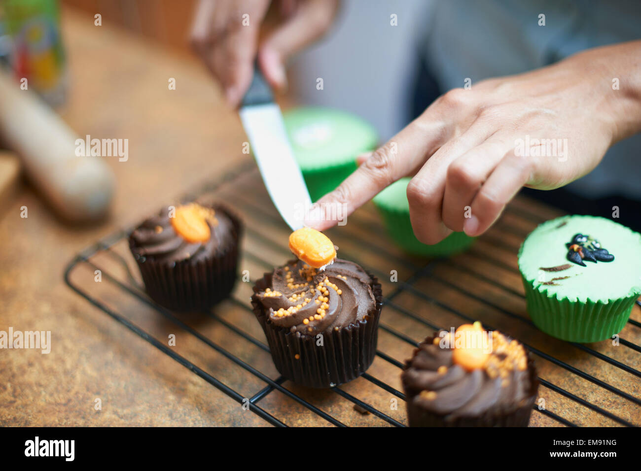 Womans hands icing cup cakes on cooling rack - Stock Image