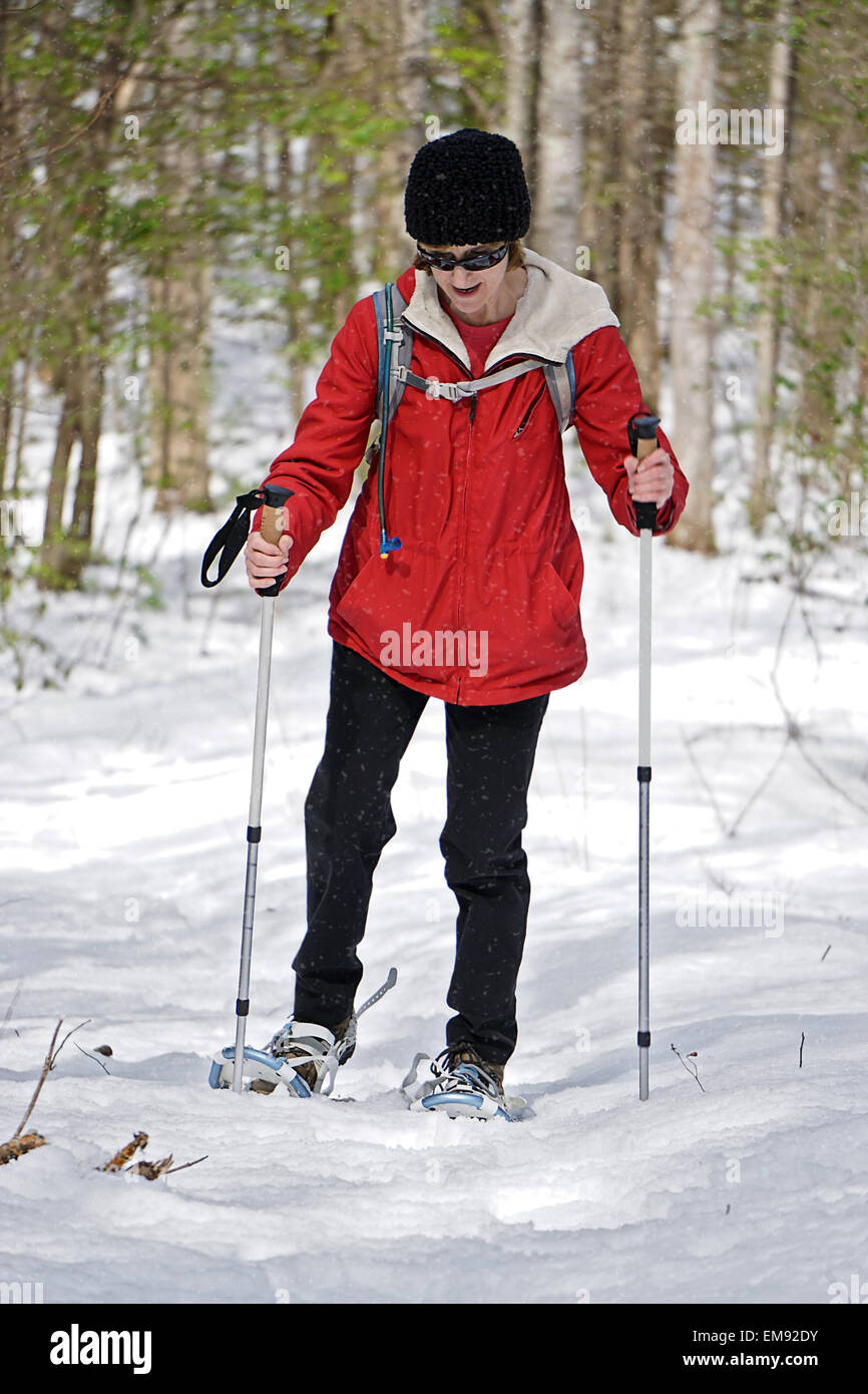A woman out for a hike in the winter snow with her snowshoes and poles. - Stock Image