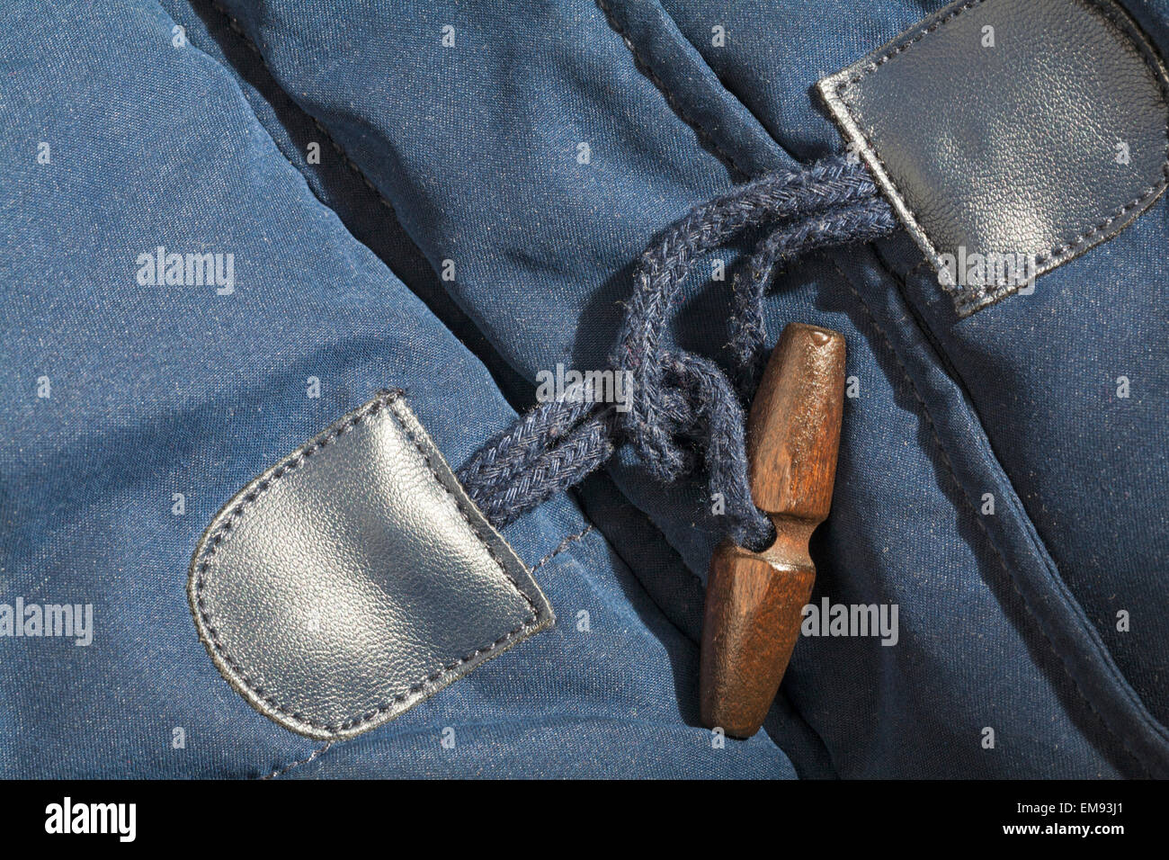 close up of toggle fastening on navy blue coat - Stock Image