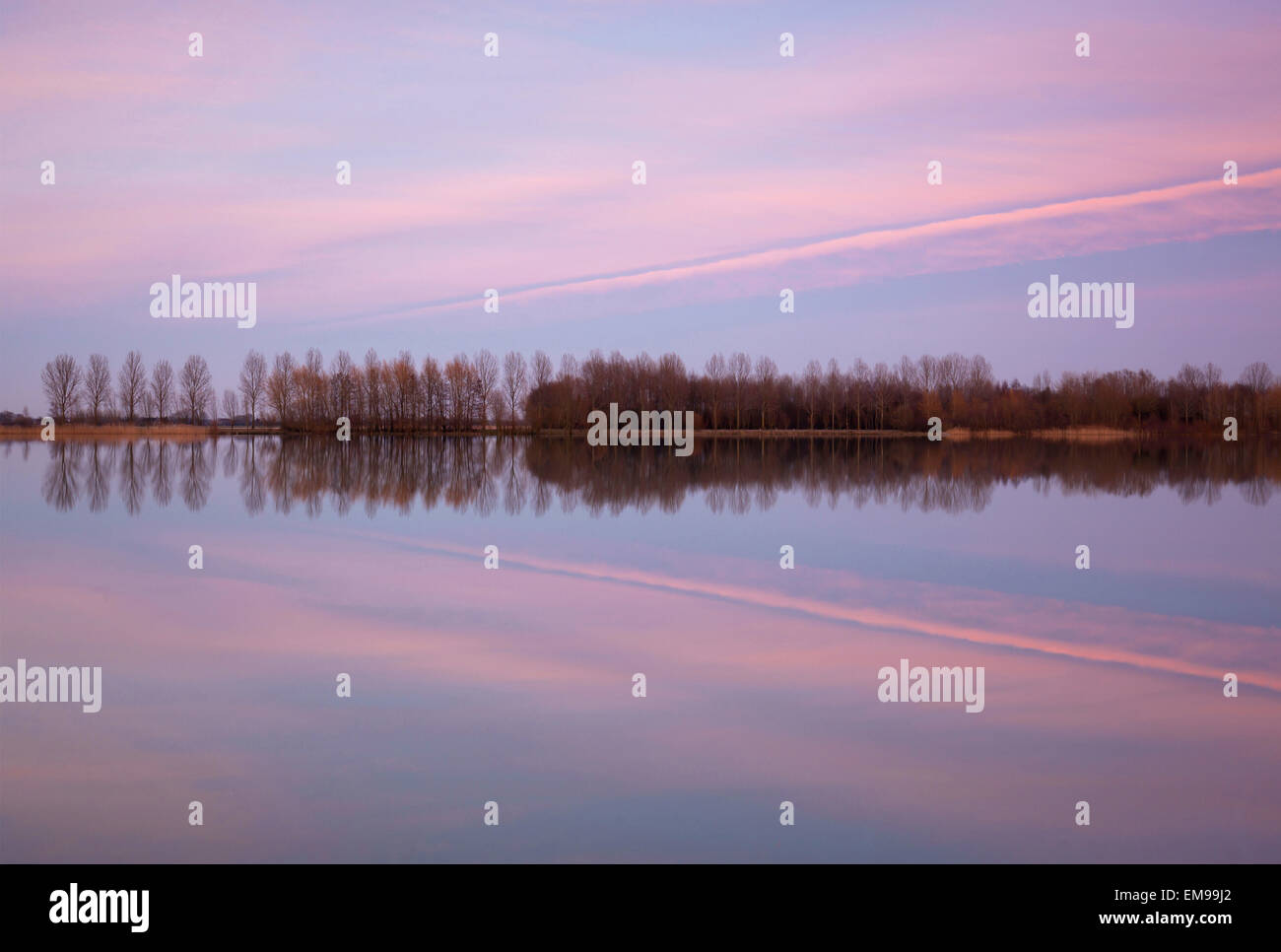Sunset over a lake with reflections in water - Stock Image