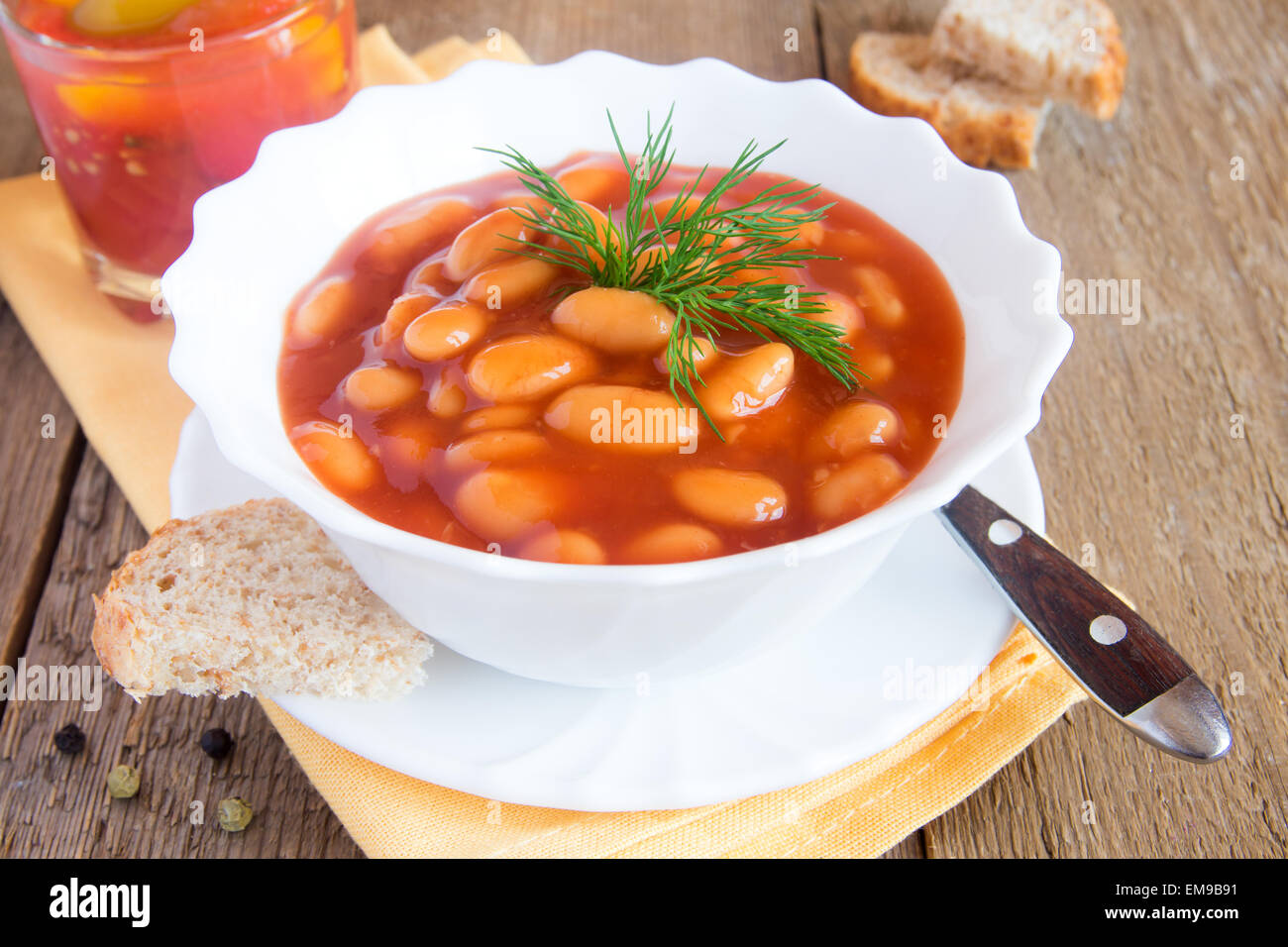 Beans in tomato sause with dill on wooden background, close up horizontal Stock Photo