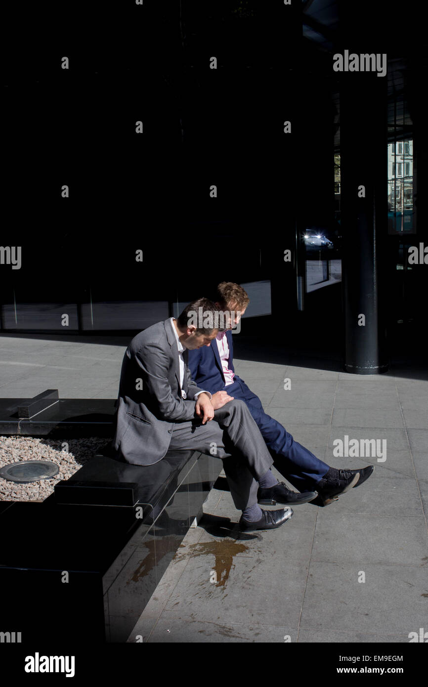 Dejected-looking businessmen sit looking at the ground in sunshine outside an office complex in the City of London. - Stock Image