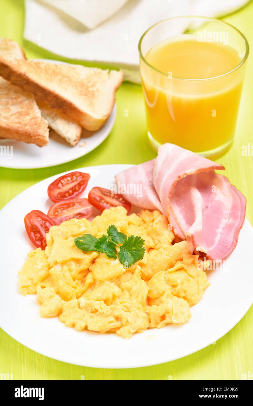 Breakfast with scrambled eggs, bacon, tomato slices, toasts and orange juice - Stock Image