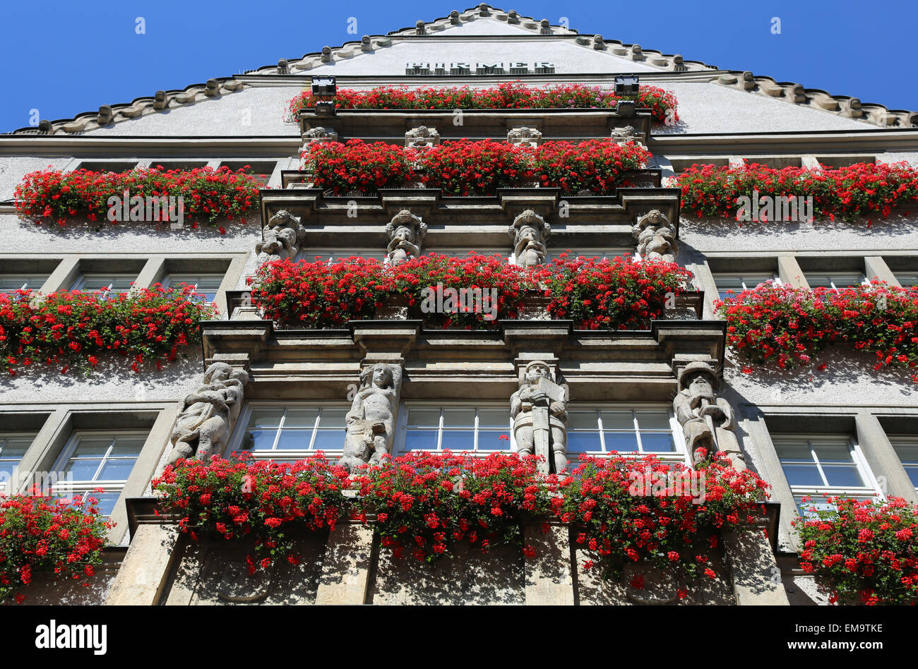 Swiss chalet with red geranium flowers in summer Stock Photo