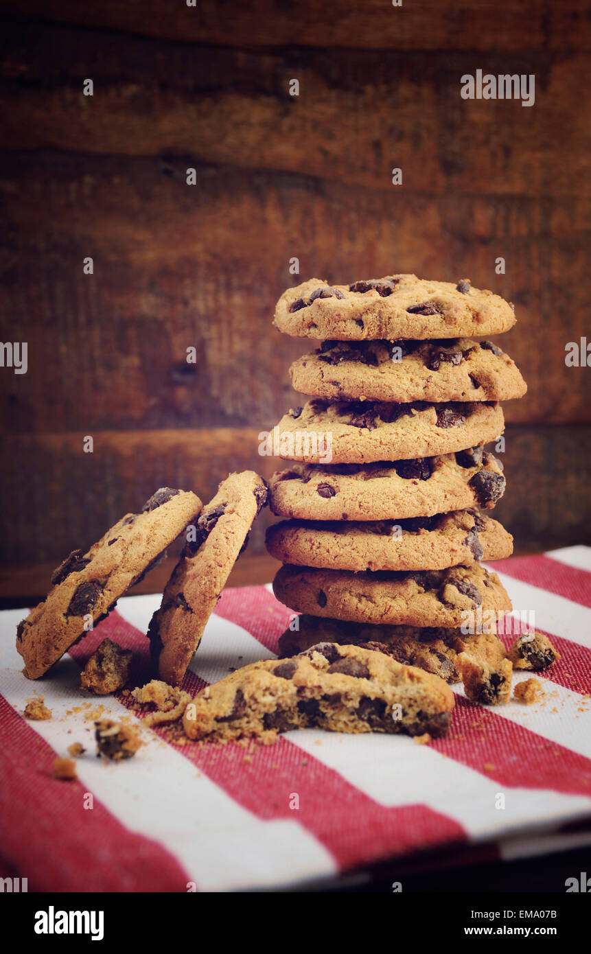 Stack of chocolate chip cookies on red and white stripe napkin against a dark wood background. - Stock Image