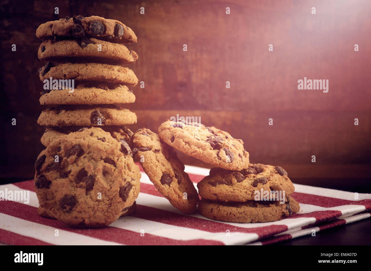 Stack of chocolate chip cookies on red and white stripe napkin against a dark wood background, with applied vintage - Stock Image