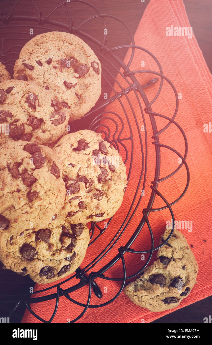 Chocolate chip cookies on vintage baking rack with orange napkin on dark wood background, with applied vintage style - Stock Image