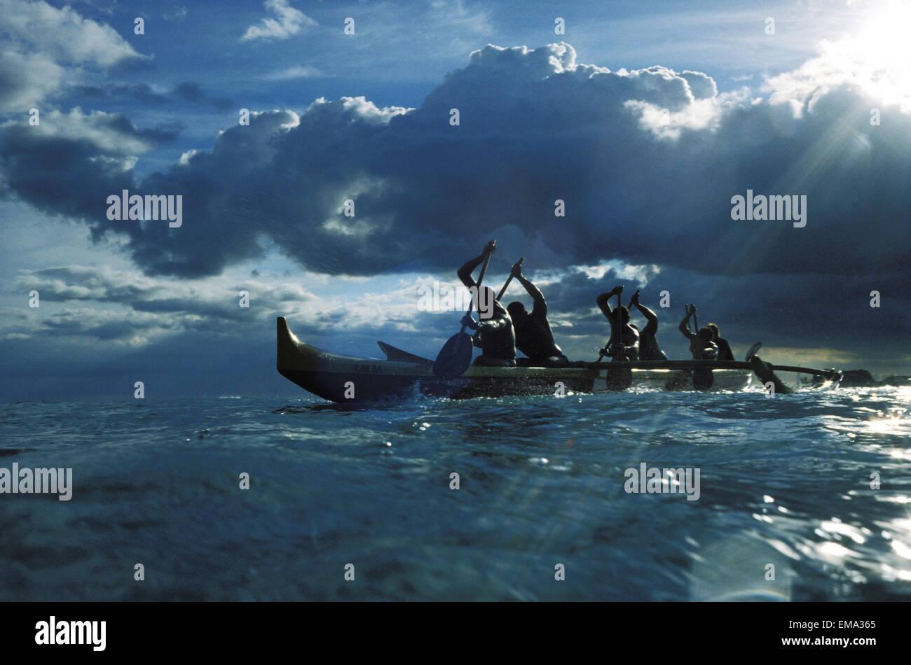 Hawaii, Ourigger Canoe Paddlers At Sunset, Rays Of Light Break Through Dramatic Sky Stock Photo
