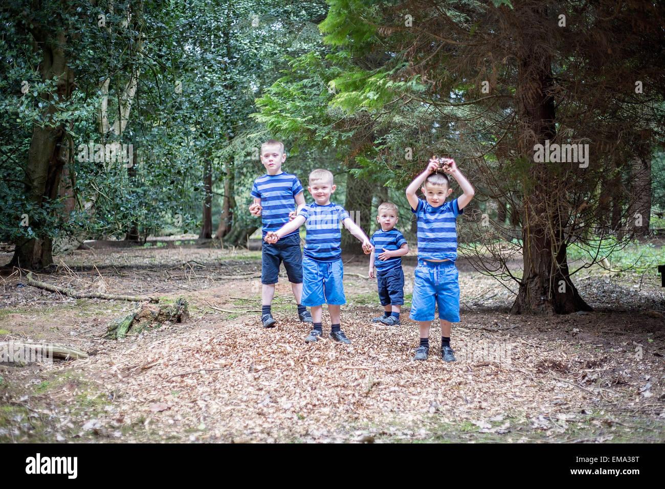 Boys playing woods matching blue running fun - Stock Image