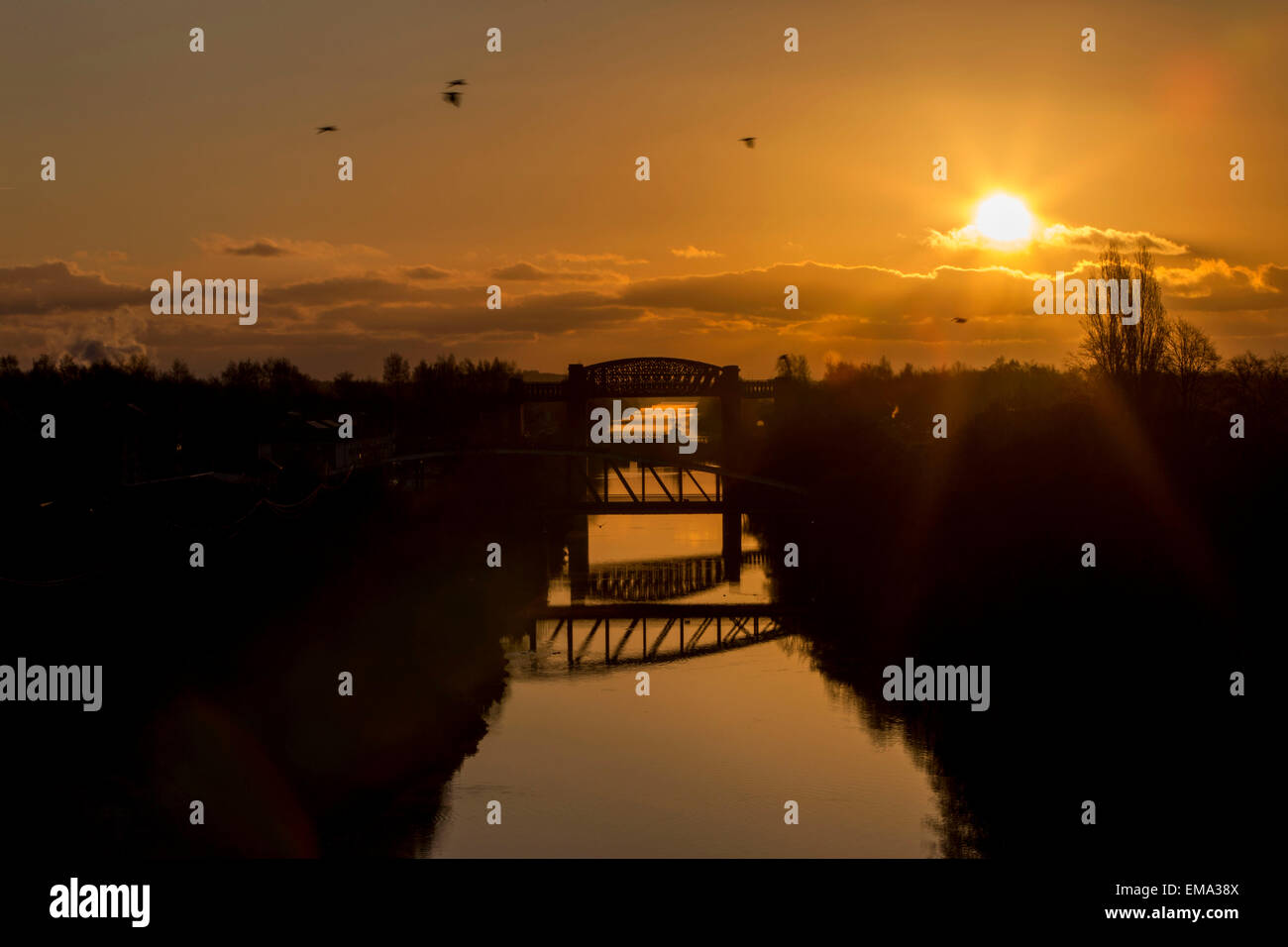 The sun rises over than Manchester Ship Canal . Picture from Stockton Heath bridge looking back towards Manchester. - Stock Image
