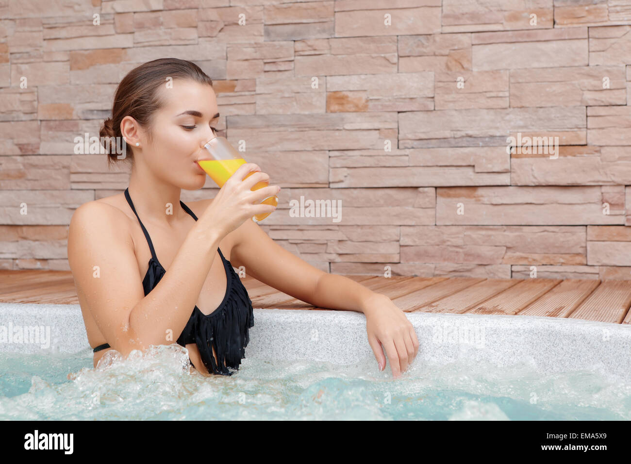 Woman spends time in a Jacuzzi - Stock Image
