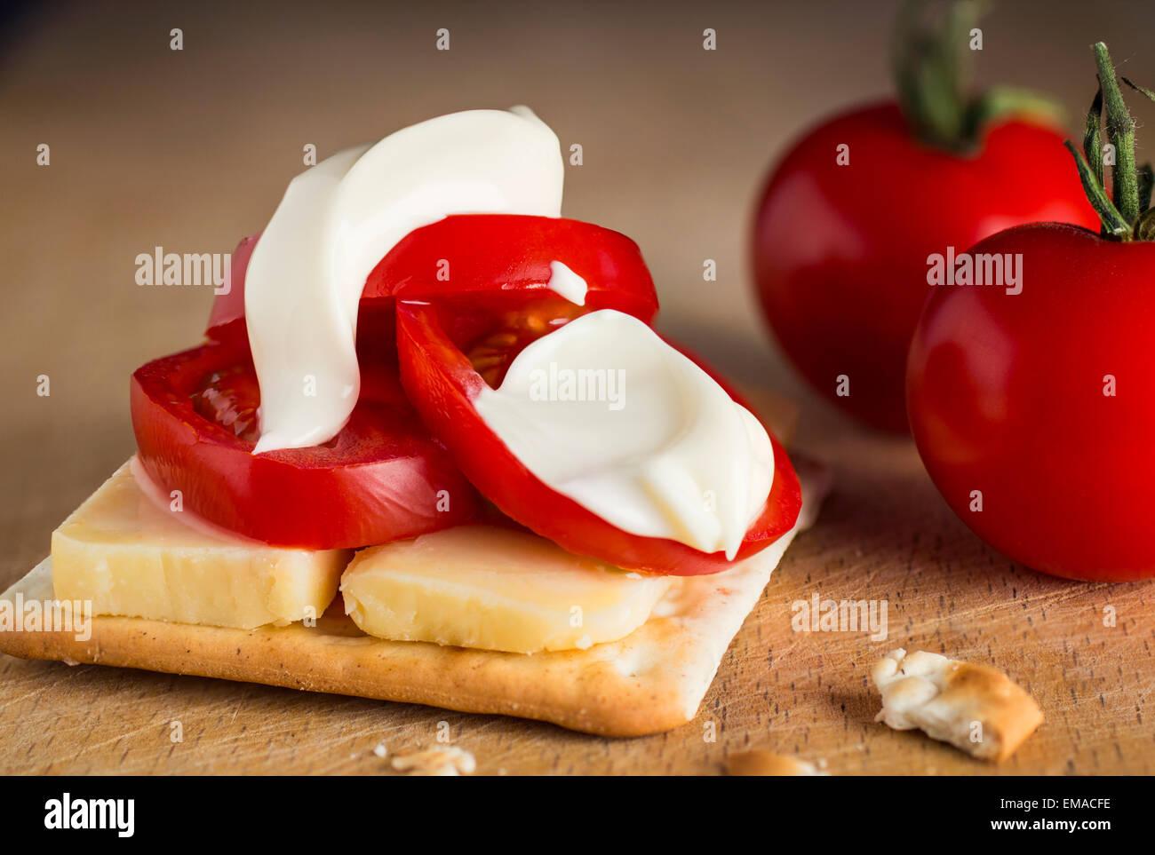 tomato cheese and mayonnaise ( mayo ) on cracker - Stock Image