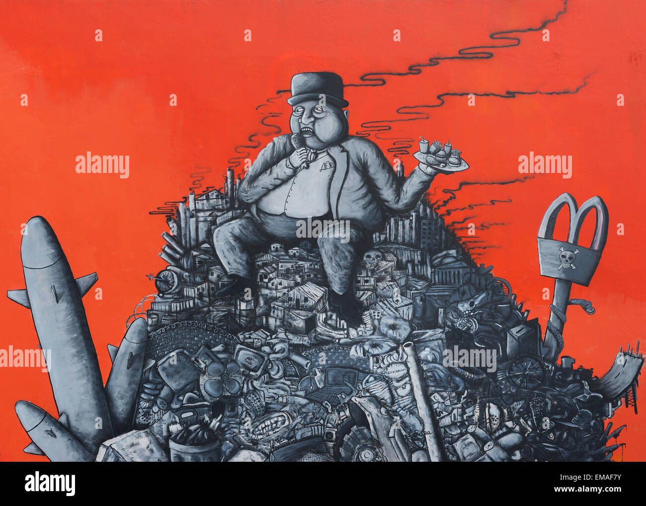 Graffiti: fat capitalist sitting on a heap of corporate junk. - Stock Image