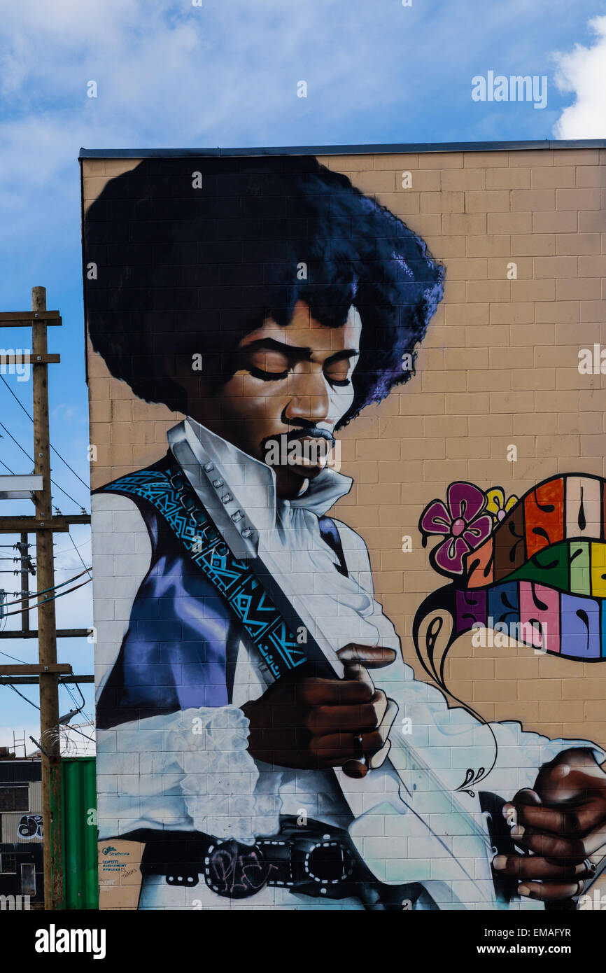 Jimmy Hendrix figure painted on the exterior wall of a building in the industrial heart of Vancouver - Stock Image