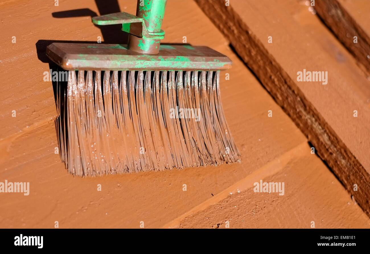 a brush being used to apply paint to a wooden fence panel england uk