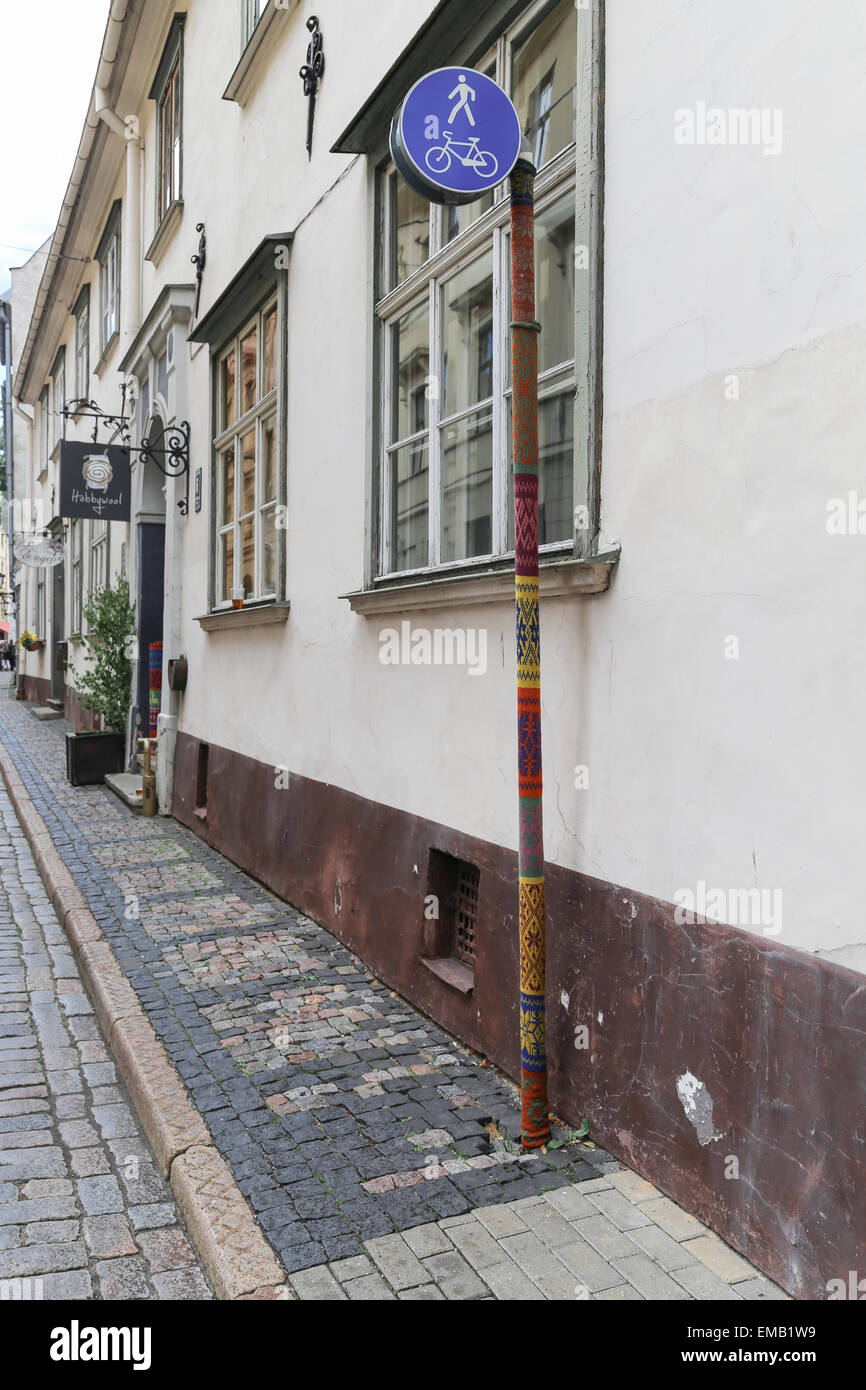 Narrow street in old town of Riga, Latvia with knitted covered pole - Stock Image