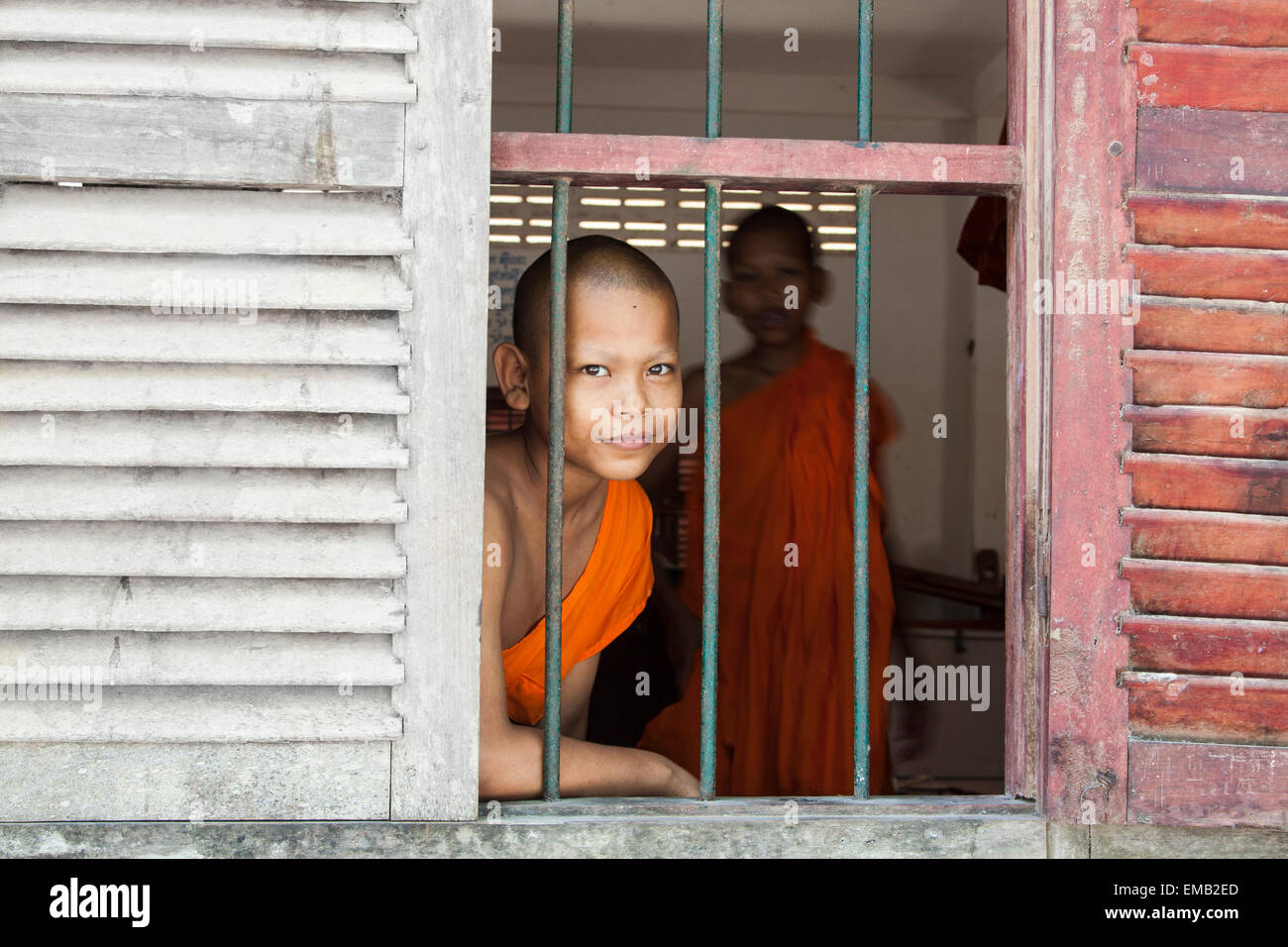 A young Buddhist monk looking through window. - Stock Image