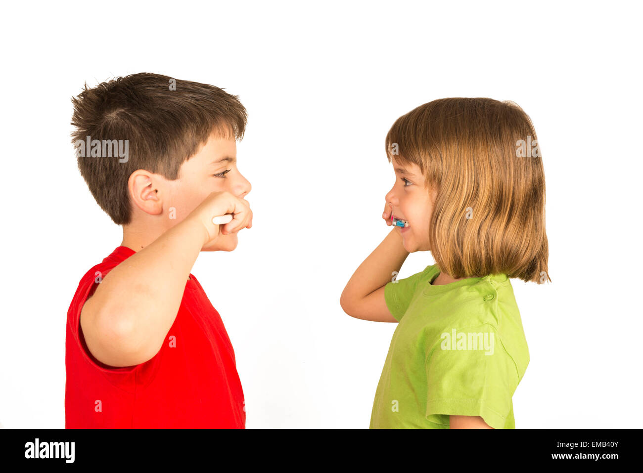 Portrait of a little girl and a young boy brushing teeth facing each other Stock Photo