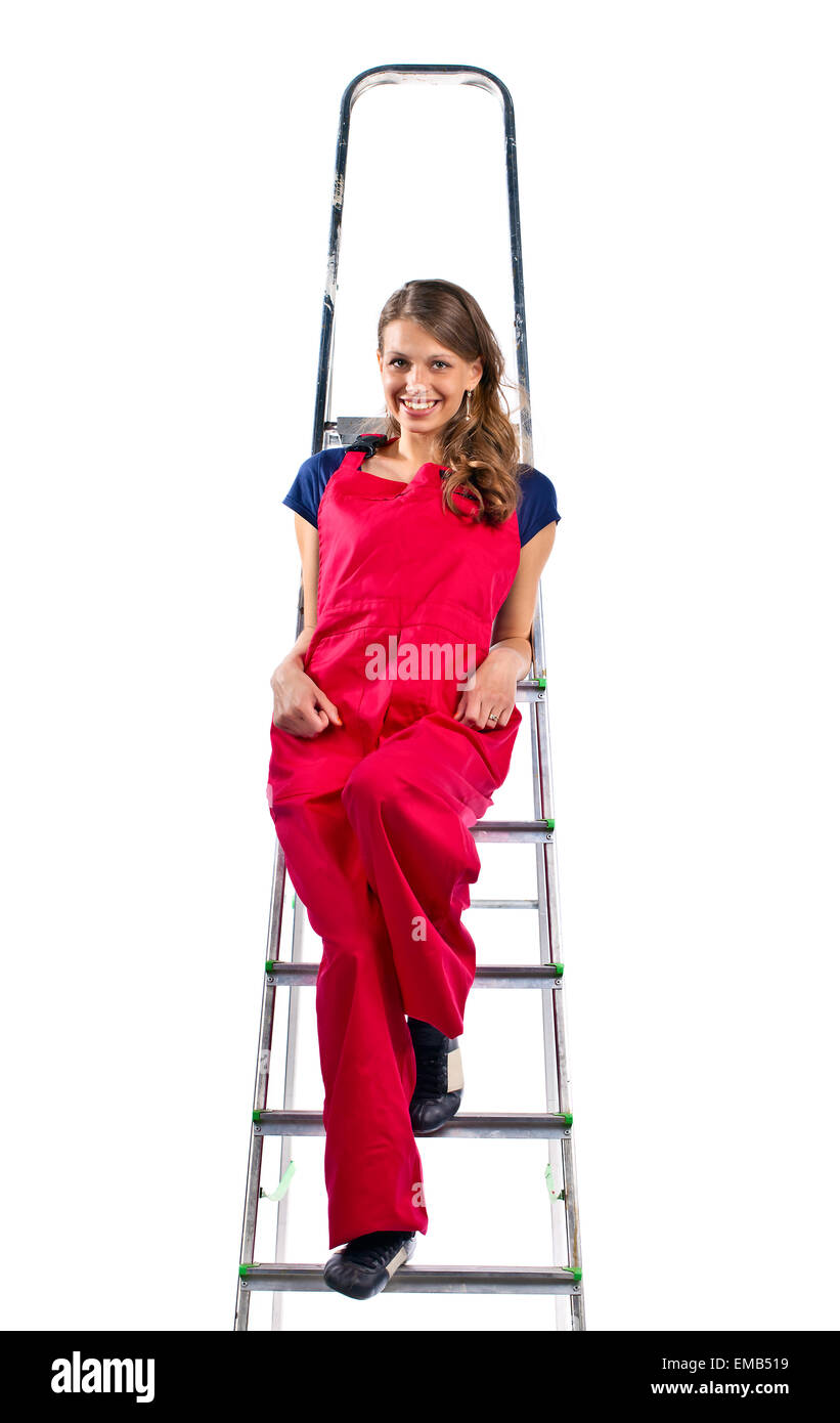 young woman in a red jumpsuit on  ladder, isolated on white - Stock Image