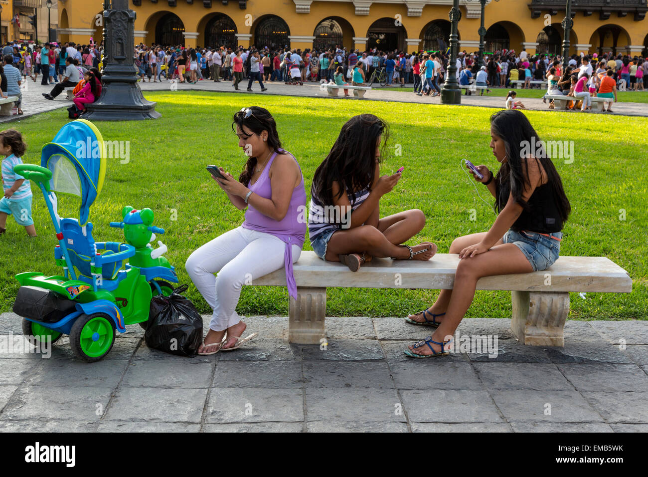 Peru, Lima.  Three Young Women Checking their Cell Phones in the Plaza de Armas, while young child walks away. - Stock Image