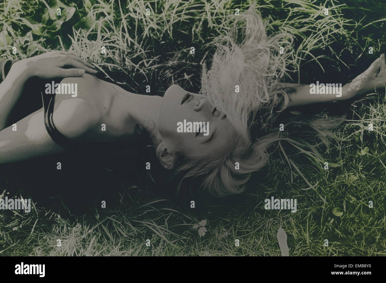 Young beautiful woman lying on the grass - Stock Image
