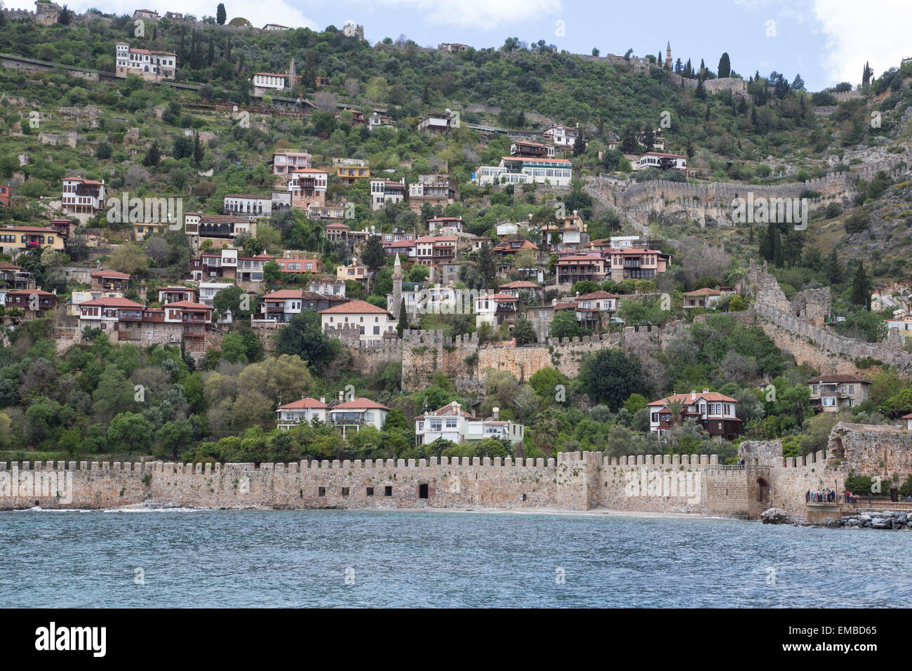 Alanya City in Turkey viewed from the harbor harbour and showing clearly the walls of the ancient fortress and battlements - Stock Image
