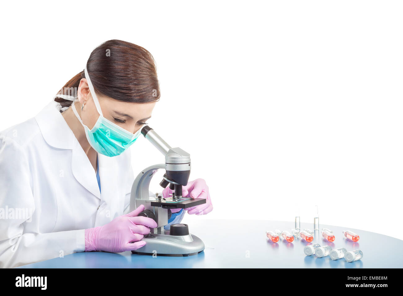 Female doctor or scientific researcher in mask using microscope in a laboratory, space for text. Stock Photo