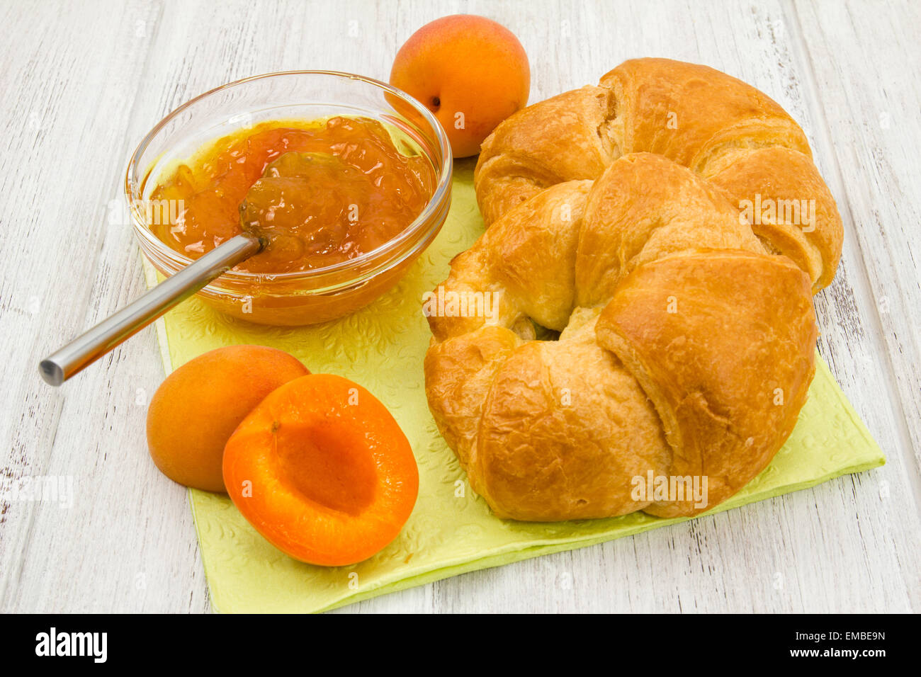 Apricot conserve, fresh apricots and croissants on white wood background - Stock Image