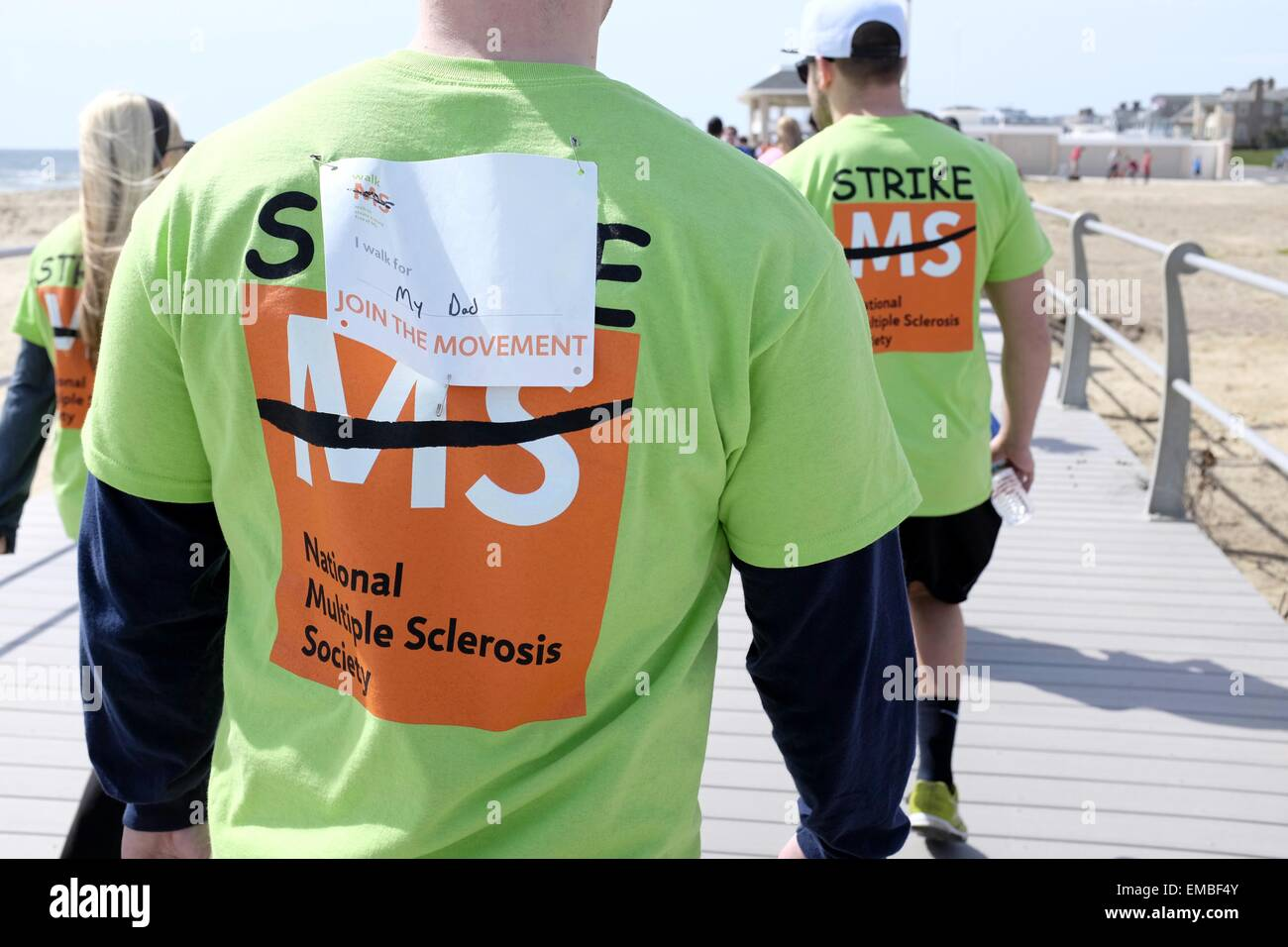 Participant in National MS Walk 2015 wearing a tag saying 'I walk for my Dad' - Stock Image