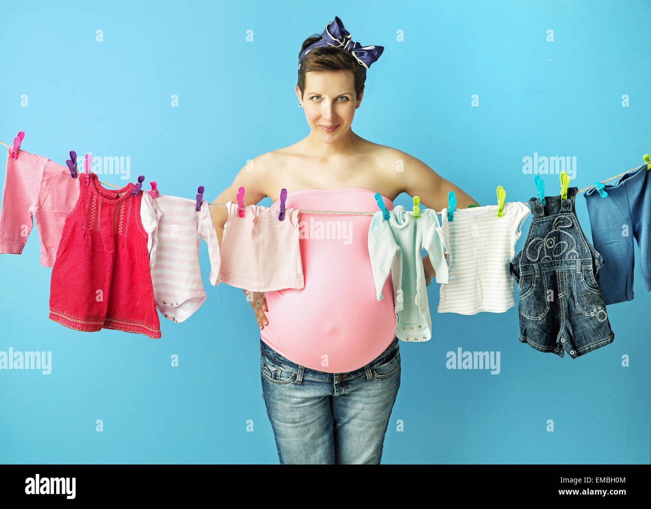 Pretty pregnant mother doing the laundry - Stock Image